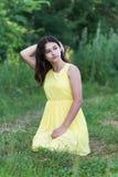 La muchacha en el vestido amarillo que se sienta en hierba Fotografía de archivo