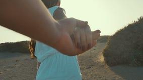La muchacha en el vestido blanco que lleva a un hombre adelante a la aventura Sígame concepto Cámara lenta Puesta del sol almacen de video
