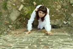 La muchacha en el vestido blanco sube la pared Foto de archivo