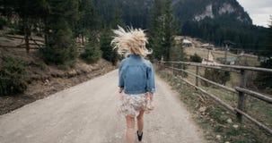 La muchacha en el vestido blanco va en el camino al país El ligar con la cámara 4K Epopeya roja metrajes