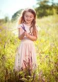 La muchacha en el vestido del melocotón en el prado con los wildflowers Fotos de archivo