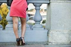 La muchacha en el vestido rojo contra la perspectiva de la verja imagenes de archivo