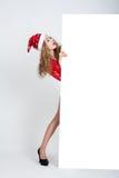 La muchacha en el vestido rojo en crecimiento completo en el sombrero de la Navidad que sostiene banderas Imagen de archivo