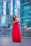 La muchacha en el vestido rojo en el fondo de rascacielos sta Fotografía de archivo