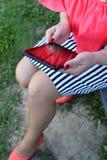 La muchacha en el vestido rojo que se sienta en un banco con la tableta Fotos de archivo