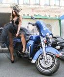La muchacha en el vestido transparente que presenta en motocicleta azul Imagen de archivo libre de regalías