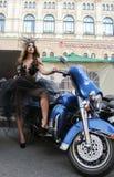 La muchacha en el vestido transparente que presenta en motocicleta azul Foto de archivo libre de regalías