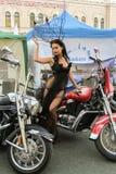 La muchacha en el vestido transparente que presenta en una motocicleta roja Foto de archivo