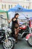 La muchacha en el vestido transparente que presenta en una motocicleta roja Imagenes de archivo