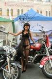 La muchacha en el vestido transparente que presenta en una motocicleta roja Imágenes de archivo libres de regalías