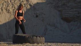 La muchacha en empujar de la mina de la arena rueda entrenamiento adentro de entrenamiento del crossfit almacen de video