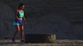 La muchacha en empujar de la mina de la arena rueda entrenamiento adentro de entrenamiento del crossfit almacen de metraje de vídeo