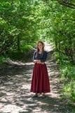 La muchacha en falda roja fotografía de archivo