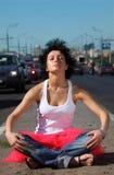La muchacha en falda rosada meditates en centro de la carretera imagen de archivo libre de regalías
