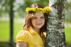 La muchacha en flores enrruella cerca de abedul Fotos de archivo