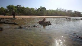 La muchacha en fregaderos del traje de baño en guitarrista del mar mira y juega almacen de video