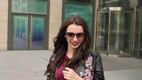 La muchacha en gafas de sol camina cerca de un edificio moderno almacen de metraje de vídeo
