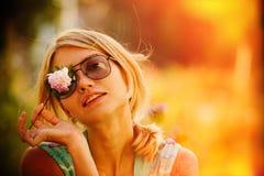 La muchacha en gafas de sol está sosteniendo una flor delante de su cara, cerrando un ojo El concepto de belleza rusa, blonde apa imagen de archivo