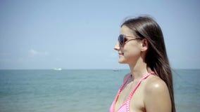 La muchacha en gafas de sol mira y admira el mar Primer 4K almacen de video