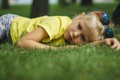 La muchacha en gafas de sol y camiseta amarilla miente en el césped Imagen de archivo libre de regalías