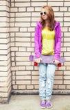 La muchacha en gafas de sol y ropa deportiva sostiene el monopatín Fotos de archivo libres de regalías