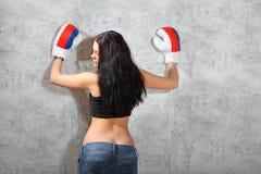 La muchacha en guantes de boxeo, asunto se inclinó para emparedar Imagen de archivo