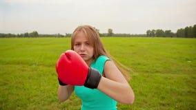 La muchacha en guantes de boxeo en un prado
