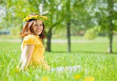 La muchacha en guirnalda se está sentando de prado Foto de archivo