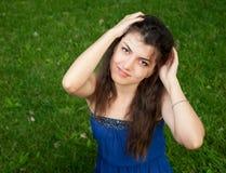La muchacha en hierba guardó su cabeza y sonrisas Imagen de archivo libre de regalías