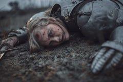 La muchacha en la imagen del arco del ` de Jeanne d en armadura miente en fango con la espada en sus manos foto de archivo libre de regalías