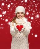 La muchacha en invierno viste con el pequeño corazón rojo Foto de archivo libre de regalías