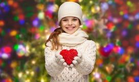 La muchacha en invierno viste con el pequeño corazón rojo Fotografía de archivo