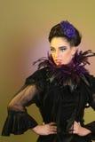 La muchacha en la alta moda compone y Fetahers Imagenes de archivo