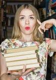 La muchacha en la biblioteca con los libros que expresan la sorpresa s de la emoción Fotografía de archivo