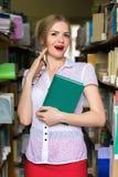 La MUCHACHA EN LA BIBLIOTECA ENTRE los estantes con los libros mira fijamente, un hermoso Fotos de archivo