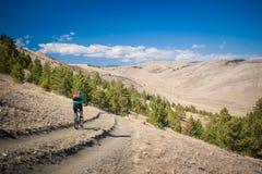 La muchacha en la bicicleta abajo de una colina escarpada Foto de archivo