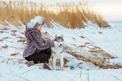 La muchacha en la capa gris al lado de un perro fornido gris en el CCB del invierno Imágenes de archivo libres de regalías