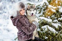La muchacha en la capa gris que sonríe al lado de un perro fornido gris en los wi Imagenes de archivo