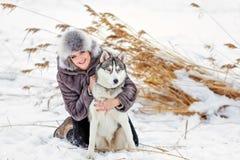 La muchacha en la capa gris que sonríe al lado de un perro fornido gris en los wi Fotografía de archivo libre de regalías