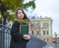 La muchacha en la cerca con un libro Imagen de archivo