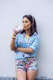 La muchacha en la ciudad en camisa que bebe un batido de leche, jugo fresco, gozando, morenita, maquillaje bronceado, sensual, re Fotografía de archivo libre de regalías