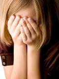 La muchacha en la edad de trece cubre su cara Fotos de archivo