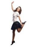La muchacha en la falda que saltaba una pierna aisló blanco Foto de archivo libre de regalías