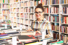 La muchacha en la librería elige el libro Foto de archivo libre de regalías