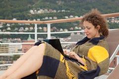 La muchacha en la manta que mentía encendido sunbed con la computadora portátil Fotos de archivo