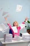 La muchacha en la oficina lanza un papel Foto de archivo