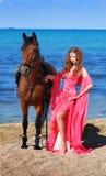 La muchacha en la playa en alineada roja Fotografía de archivo libre de regalías