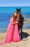 La muchacha en la playa en alineada roja Fotos de archivo