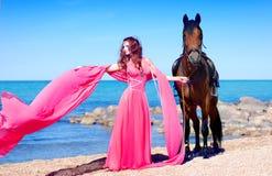 La muchacha en la playa en alineada roja Foto de archivo libre de regalías