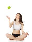La muchacha en la posición de loto lanza la manzana Imagenes de archivo